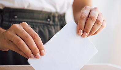 woman placing ballot box 394x229
